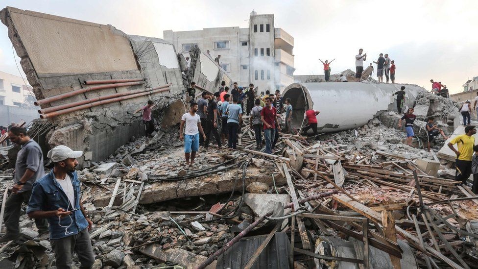 Palestinians search the remains of a cultural centre destroyed in an Israeli air strike on Gaza (9 August 2018)