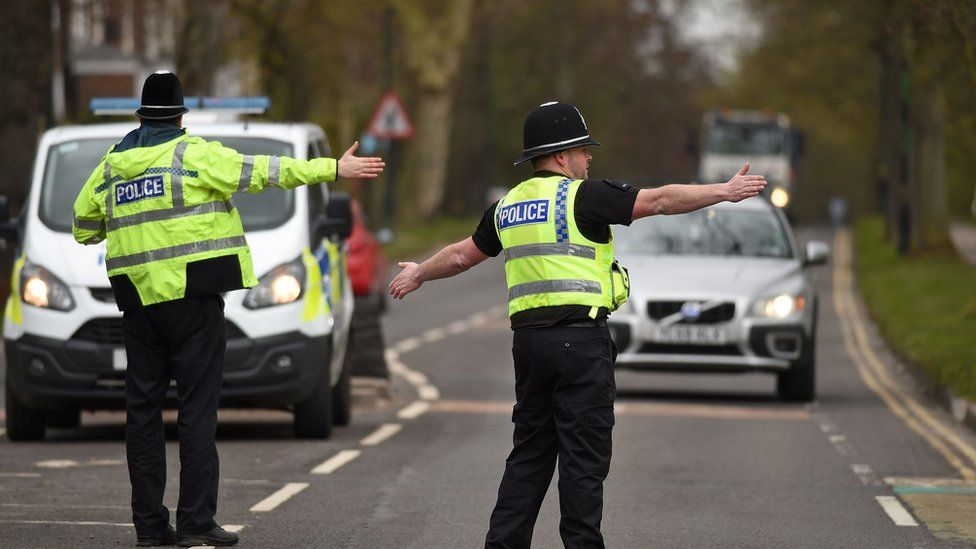 """Police officers from North Yorkshire Police stop motorists in cars to check that their travel is """"essential"""", in line with the British government's Covid-19 advice to """"Stay at Home"""", in York, northern England"""
