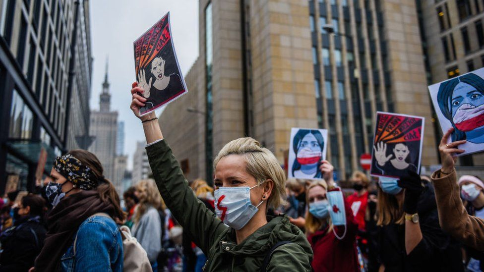 A woman wears a protective face mask and holds a banner as she participates in a National strike for the seventh day of protests against the Constitutional Court ruling