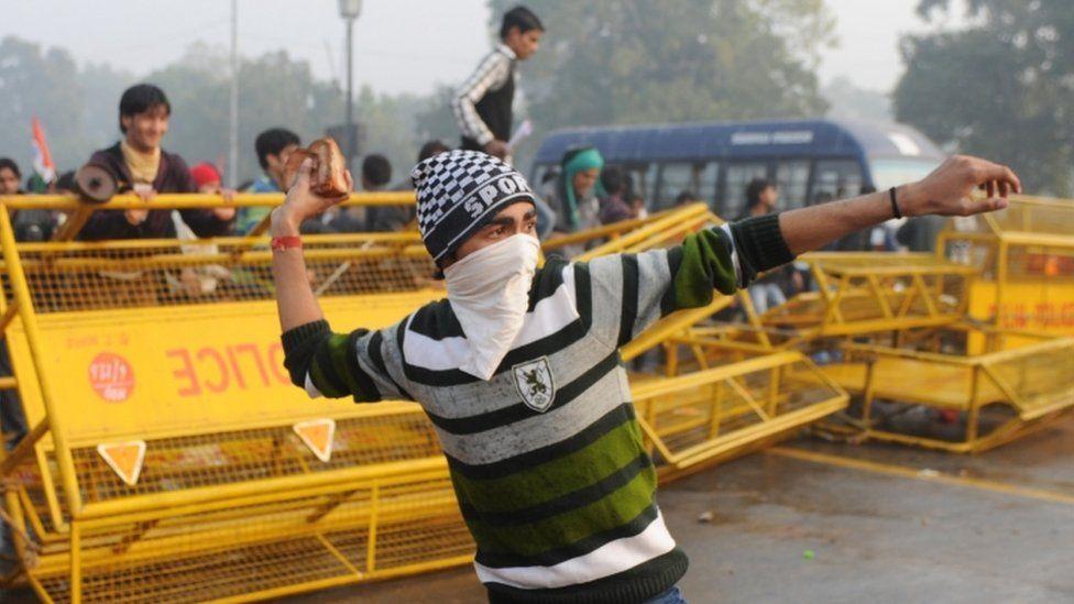 Indian protestor hurling rock during demonstration