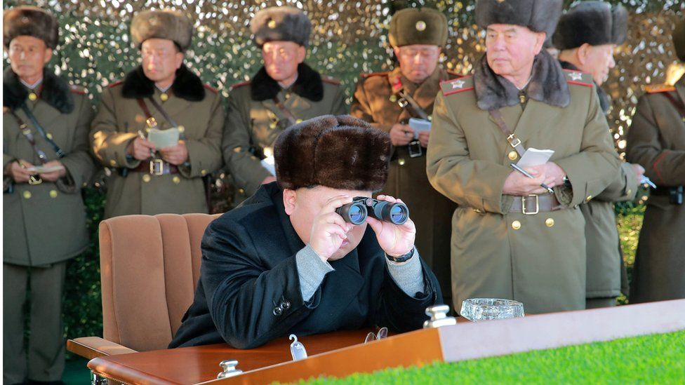 North Korean leader Kim Jong Un looks through binoculars at a firing contest among army multiple launch rocket system (MLRS) batteries in an undated photo released by North Korea's Korean Central News Agency (KCNA) in Pyongyang on December 21, 2016.