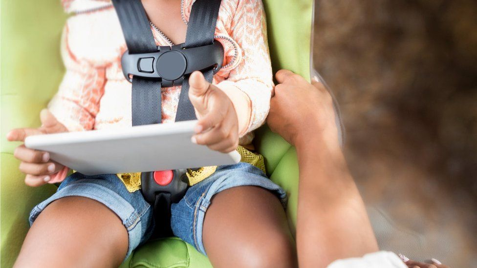 Child in car with tablet