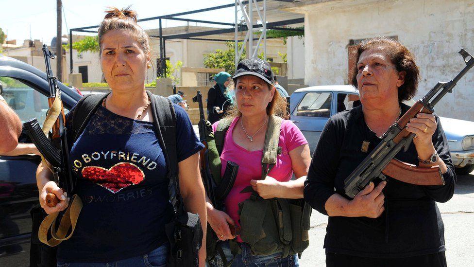 Women hold rifles inside the Lebanese village of Qaa on 28 June 2016