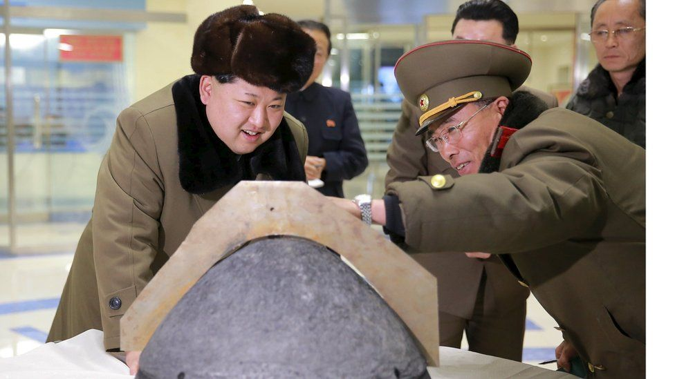 North Korean leader Kim Jong-un looks at a rocket warhead tip after a simulated test of atmospheric re-entry of a ballistic missile