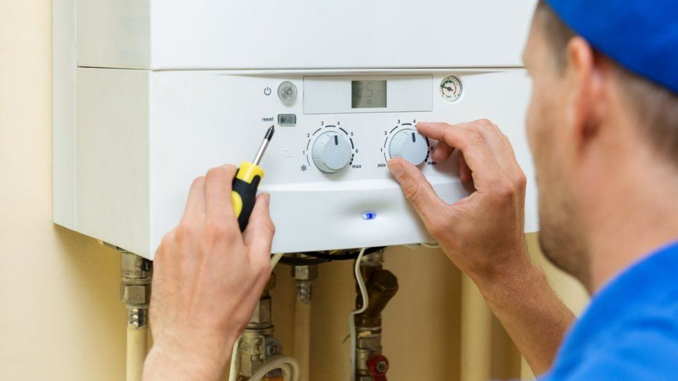 worker set up central gas heating boiler at home - stock photo