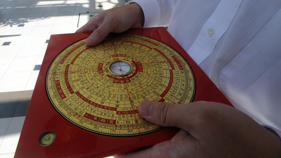 Feng Shui master Jet Li shows the reading from a compass for a building entrance in Singapore on January 21, 2009