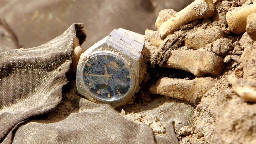 A wrist watch is seen on a human skeleton and clothes from persons allegedly executed during the regime of former President Saddam Hussein