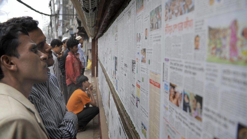 Men reading newspapers in Bangladesh