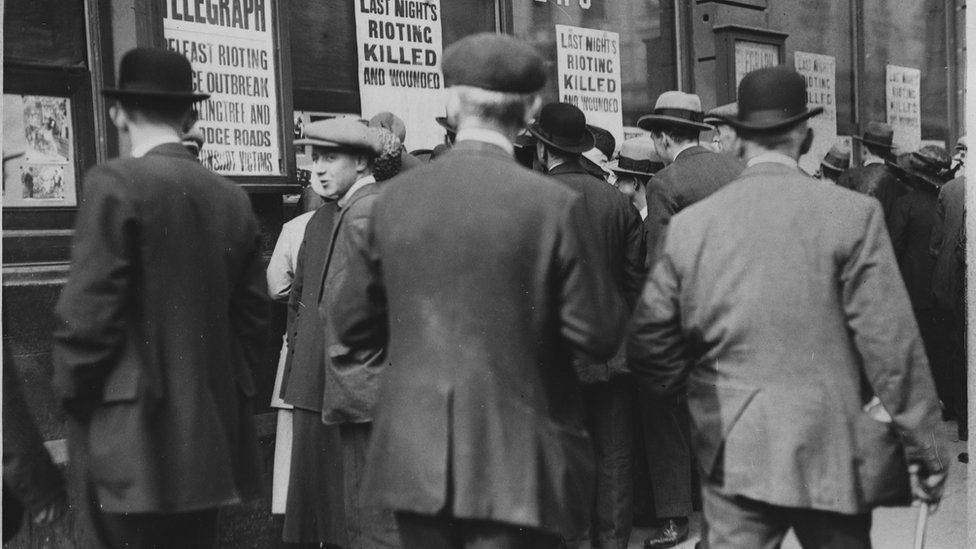 People gather outside the Belfast Telegraph offices to check through lists of those killed during rioting in 1920