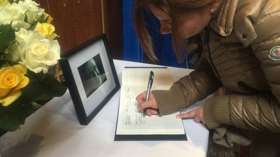 Woman signing condolence book