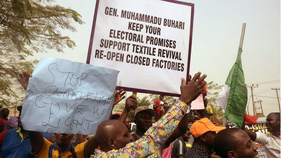 People holding placards in a February demonstration asking President Buhari to keep electoral promises of a textile revival by re-opening closed factories.