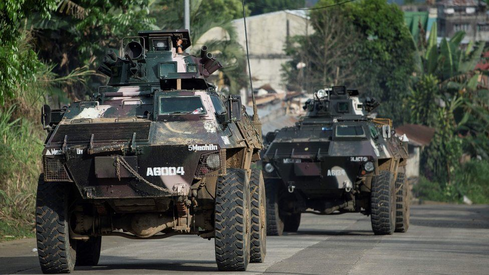 Armoured personnel carriers drive down a village road in Marawi, on the southern island of Mindanao