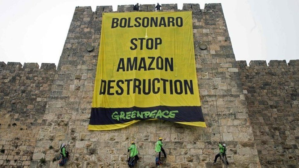 Greenpeace activists hang a large banner on the ramparts of the Old City of Jerusalem with a message to the visiting Brazilian president, on April 1, 2019