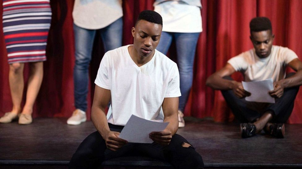 Staged photo depicting actors reading scripts