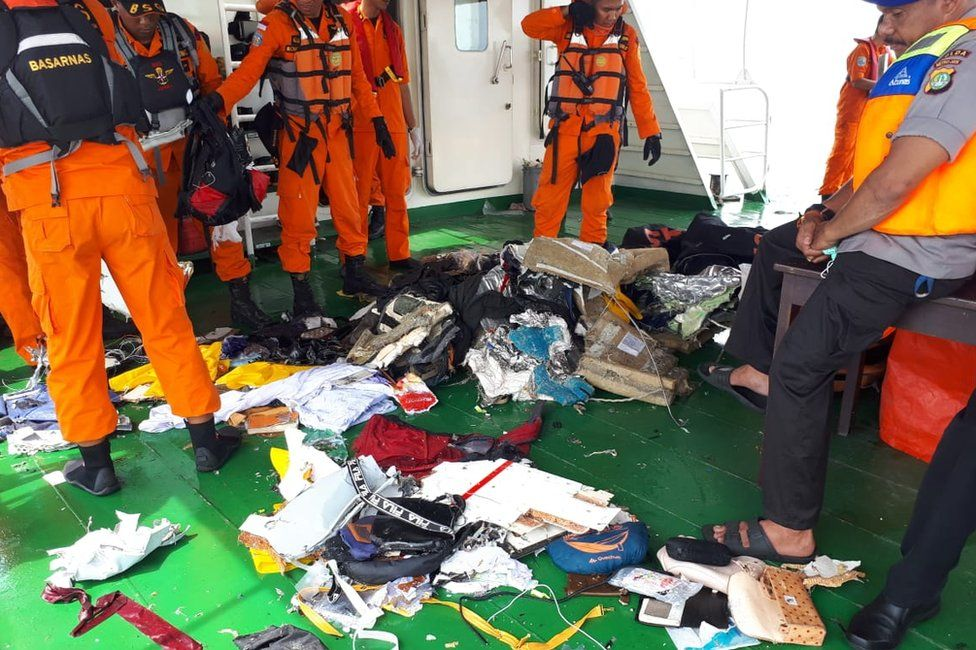 Search and rescue officials stand next to belongings salvaged from the sea
