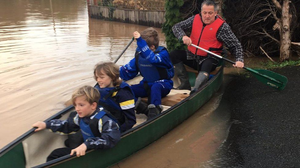 Alun Thomas with Ioan, Bowen and Harri sitting in a small boat