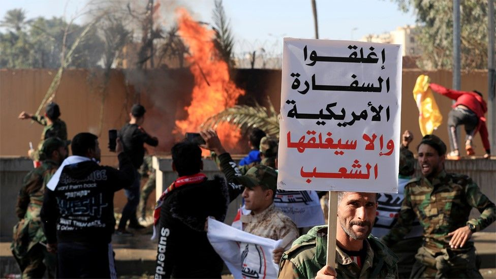 """A man holds up a sign saying """"Close the American embassy or people will close it"""" as protesters set fire to the wall of the US embassy compound in Baghdad, Iraq (31 December 2019)"""