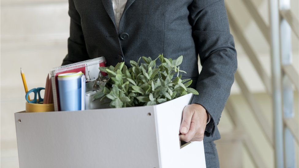 Woman walking out of office with box