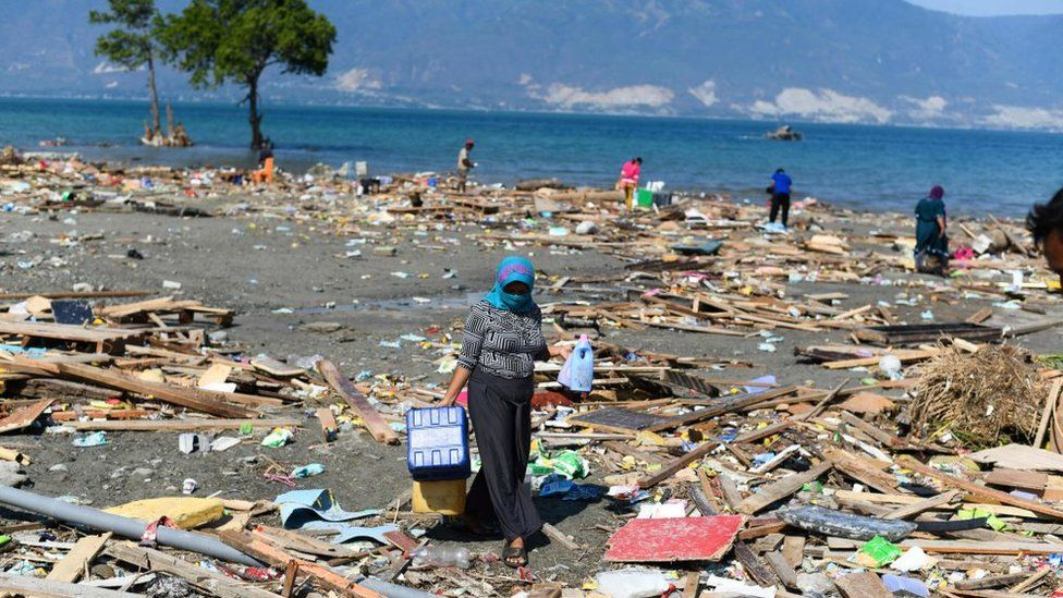 A survivor salvages useable items from debris in Palu, Indonesia's Central Sulawesi on October 1, 2018, after an earthquake and tsunami hit the area on September 28.