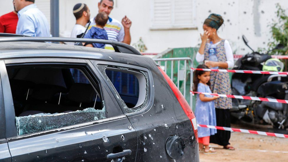Israelis stand near a car damaged by a rocket fired from Gaza (9 August 2018)