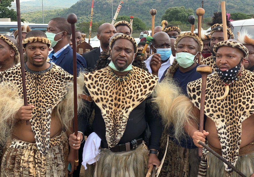 Men dressed in leopard hide according to custom