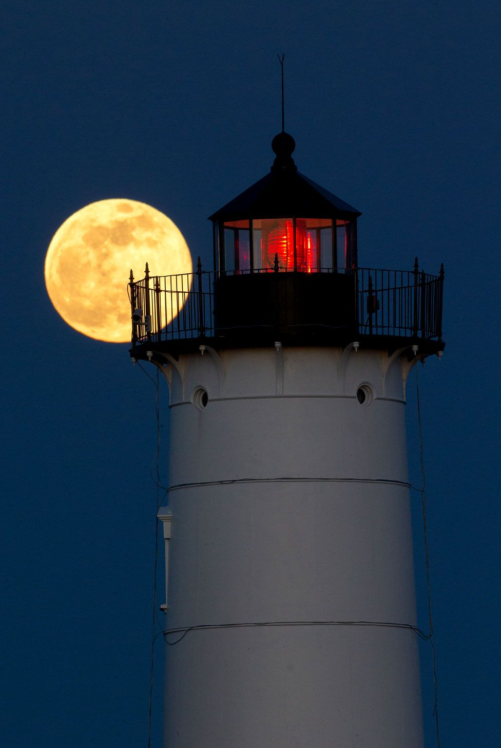 The supermoon rising behind the Nubble Lighthouse on Cape Neddick, in York, Maine, US