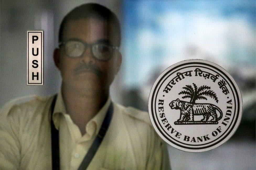 An employee walks behind the Reserve Bank of India (RBI) logo inside its headquarters in Mumbai, India, October 5, 2018
