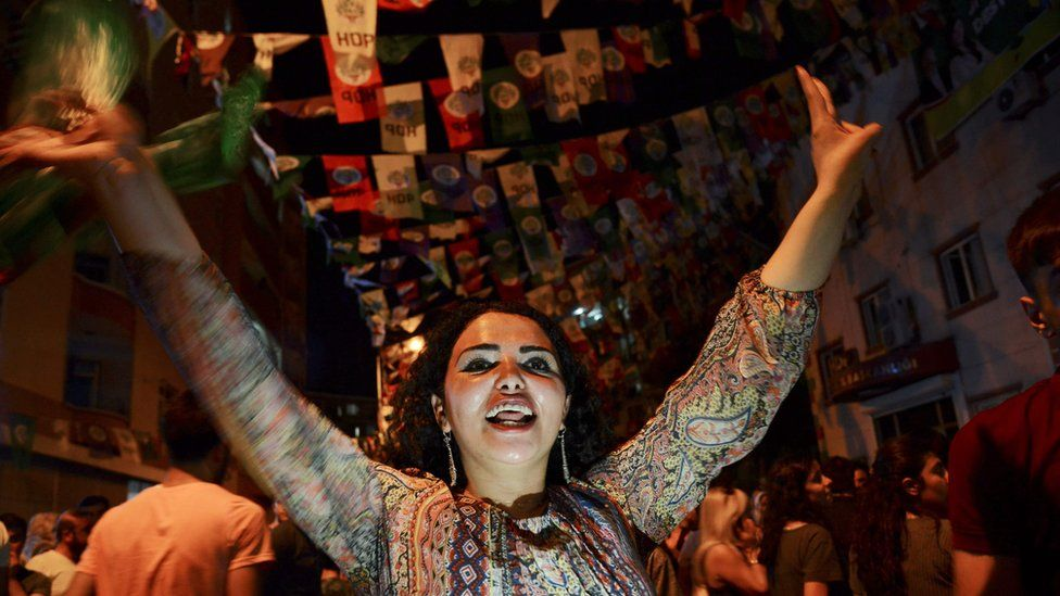 Women dance under election banners of the HDP in the mainly-Kurdish city of Diyarbakir