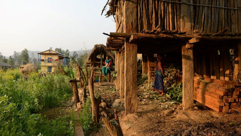 Nepalese women, pictured in February 2017, look at a Chhaupadi hut in Surkhet District