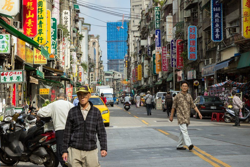 People and vehicles at a street and buildings full of signboards in Taipei, Taiwan.