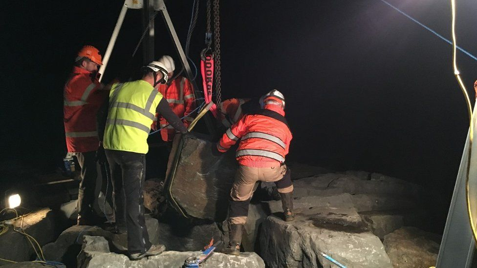 The boulder being moved