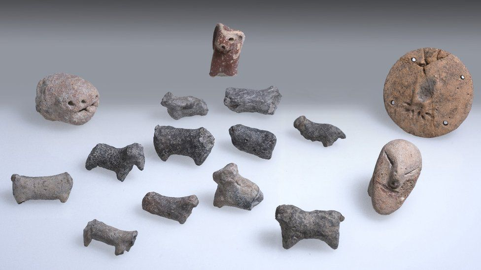 A collection of 15 small figurines made of stone, most shaped like people or animals