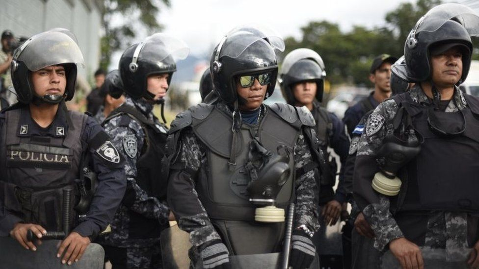 Police officers belonging to the COBRA Special Riot Command stand guard next to supporters of opposition candidate Salvador Nasralla as they hold a protest march on December 6, 2017 in Tegucigalpa.