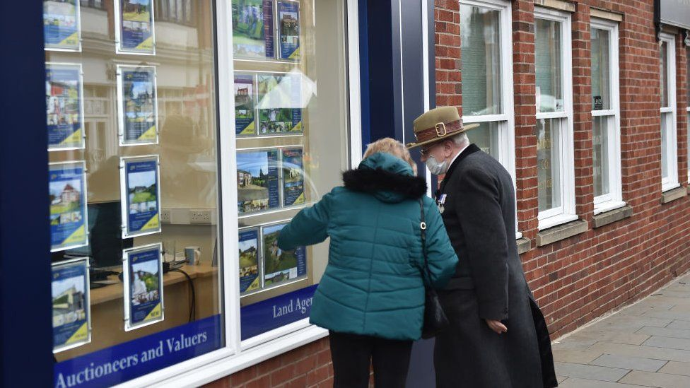 Couple looking at housing in estate agent in masks