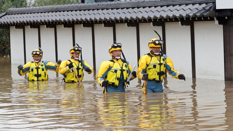 Police search a flooded area in the aftermath of Typhoon Hagibis,