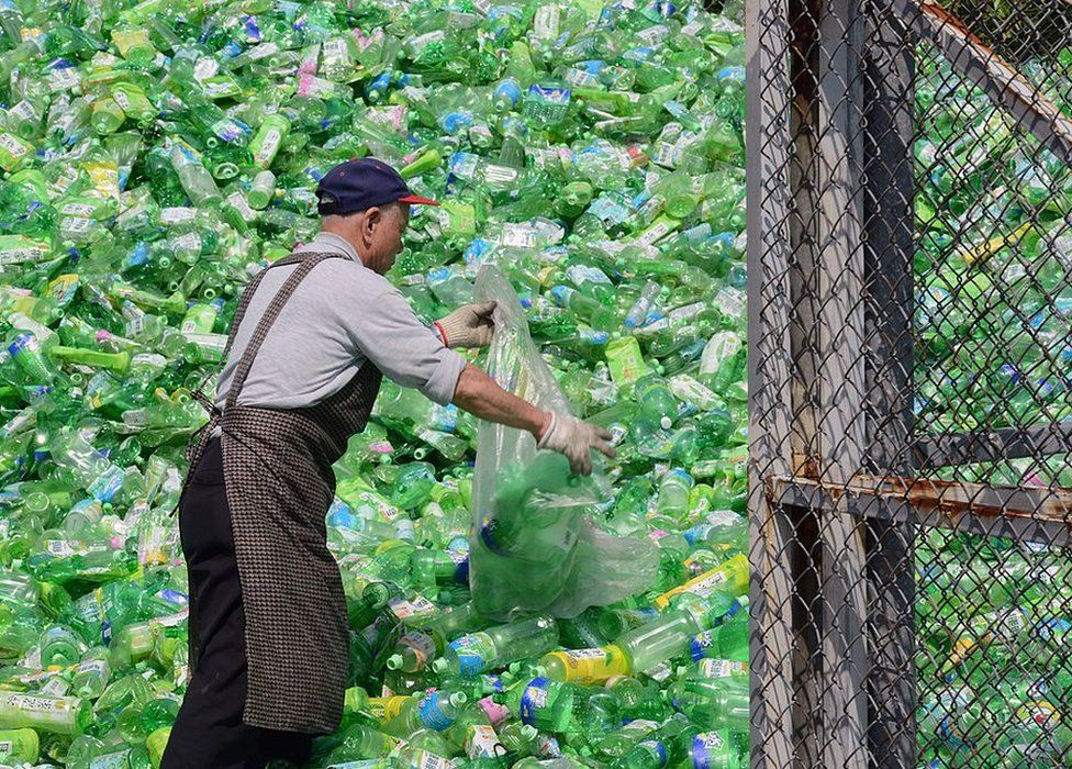 A volunteer sorts through plastic bottles at a recycling plant in Taipei, Taiwan