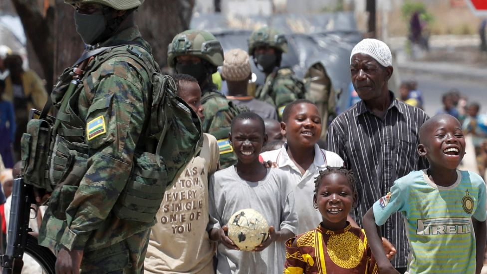 Children displaced by fighting walk past soldiers from the Rwandan security forces in a camp for the internally displaced, in the town of Quitunda, Mozambique - 22 September 2021