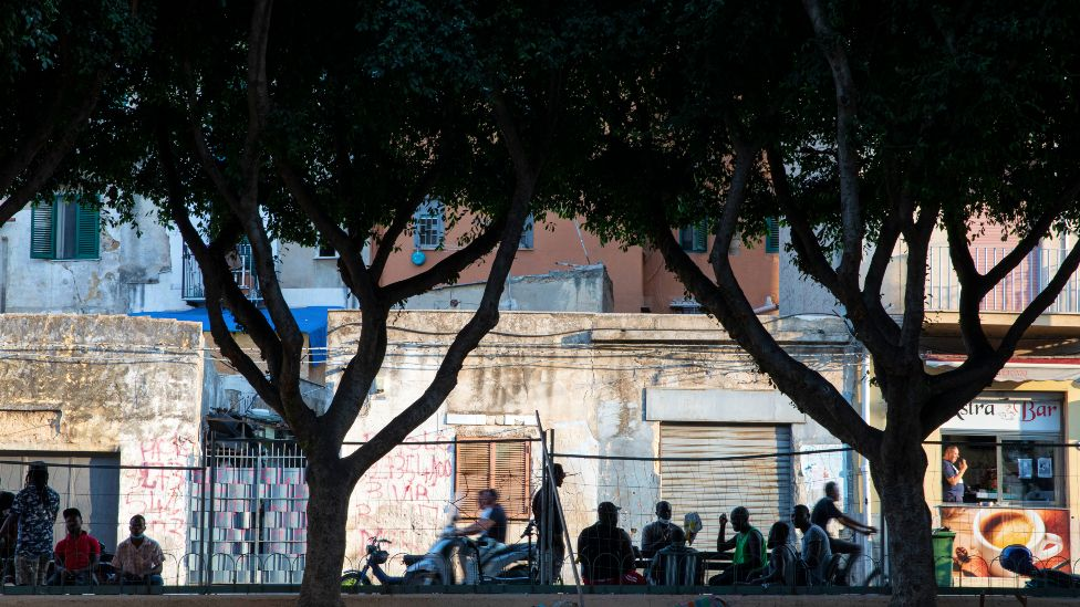 Migrants sitting at outside tables in alermo's Ballarò neighbourhood - Sicily