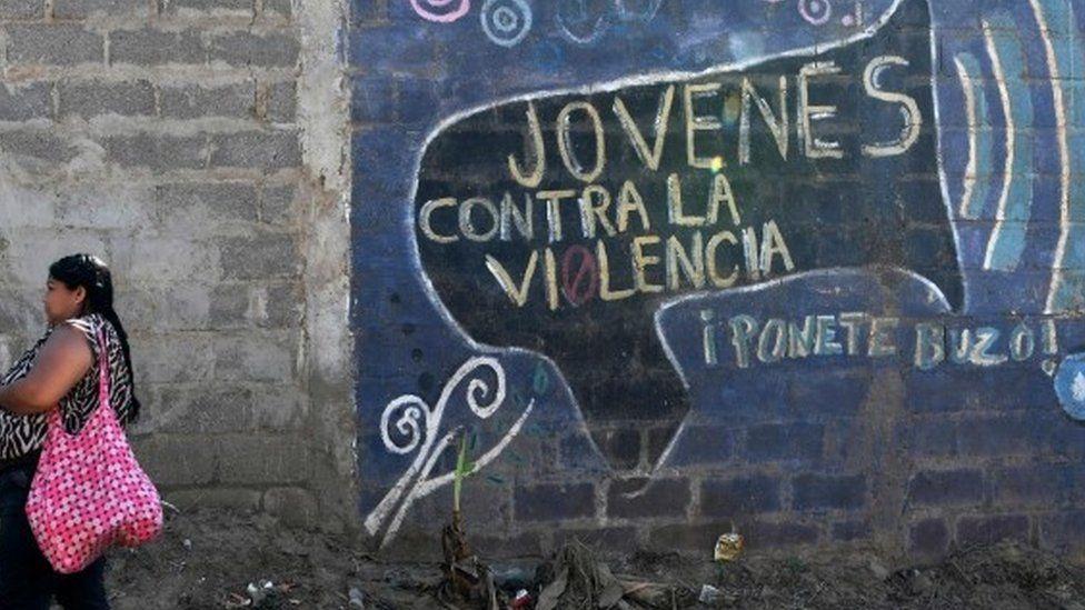 Woman next to mural in Tegucigalpa, Honduras
