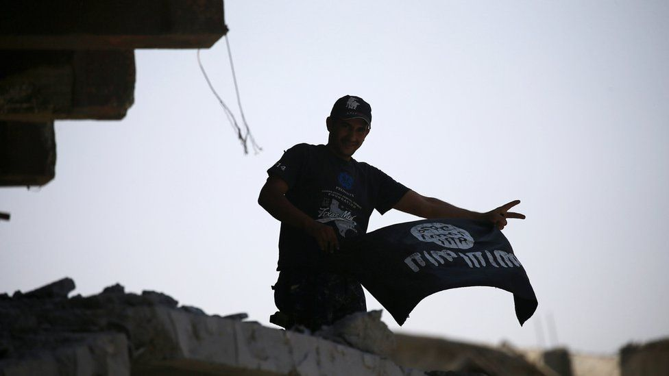 A member of Iraqi security forces celebrates as he holds a flag of Islamic State militants on the top of a destroyed building from clashes in the Old City of Mosul, 10 July