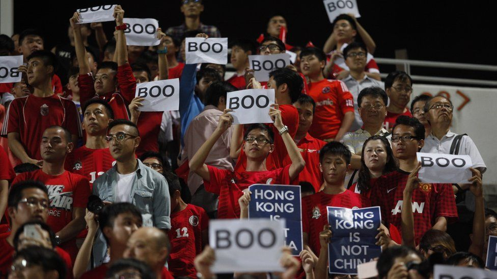 Hong Kong fans hold up signs that read 'Boo' while the national anthem was being played during a world cup qualifier at Mong Kok stadium in Hong Kong on November 17, 2015.