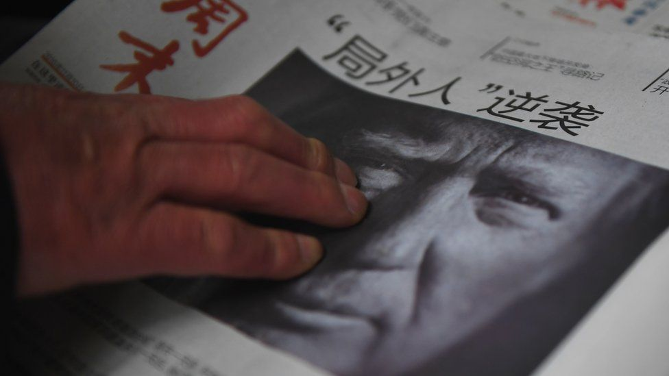 A man buys a Chinese newspaper, with the headline that reads 'Outsider strikes back