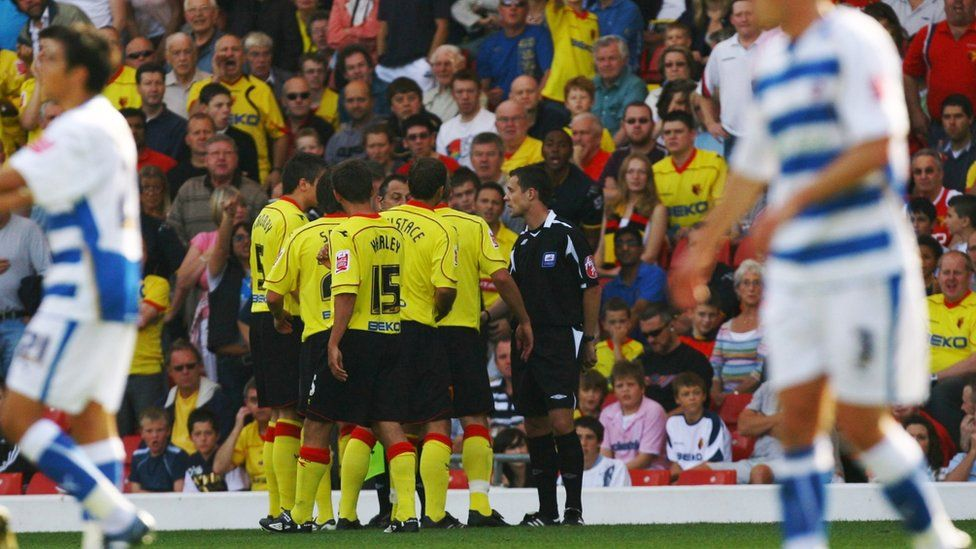 Referee Stuart Attwell surrounded by Watford players