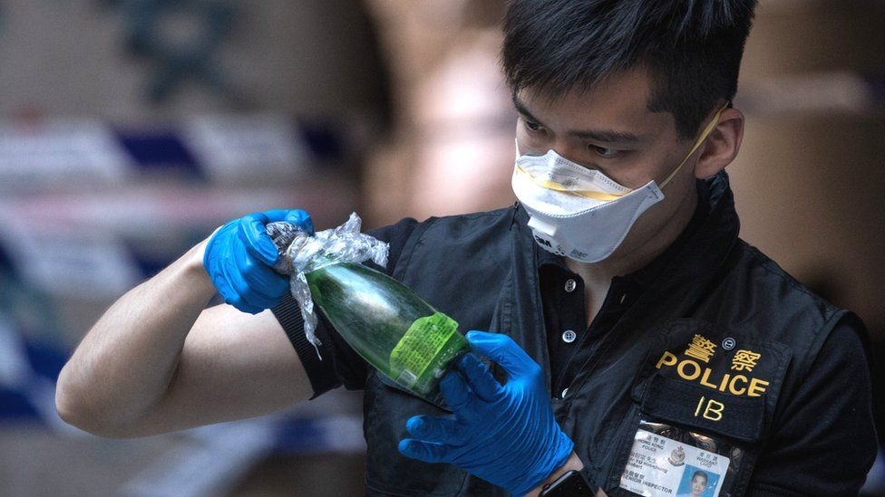 Hong Kong police officer inspects petrol bomb