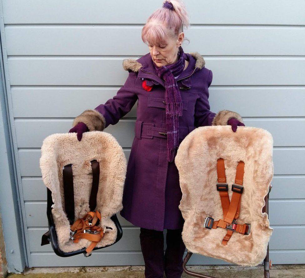 Mel Kirkpatrick holding her children's old car seats