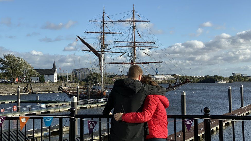 A couple hold one another looking out over Cardiff Bay