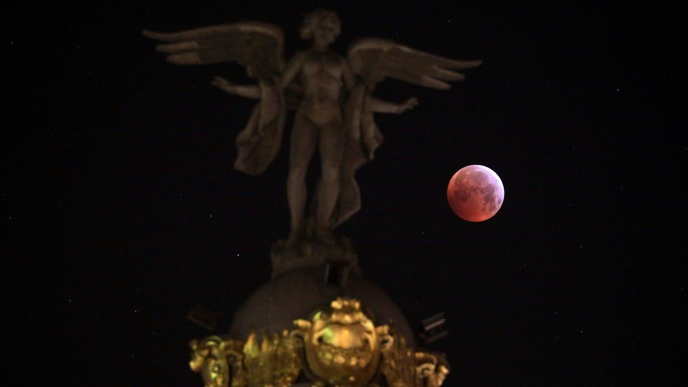 "The moon is seen beside ""Victoria Alada"" statue on the top of Metropoli building during a total lunar eclipse, known as the ""Super Blood Wolf Moon"" in Madrid, Spain"