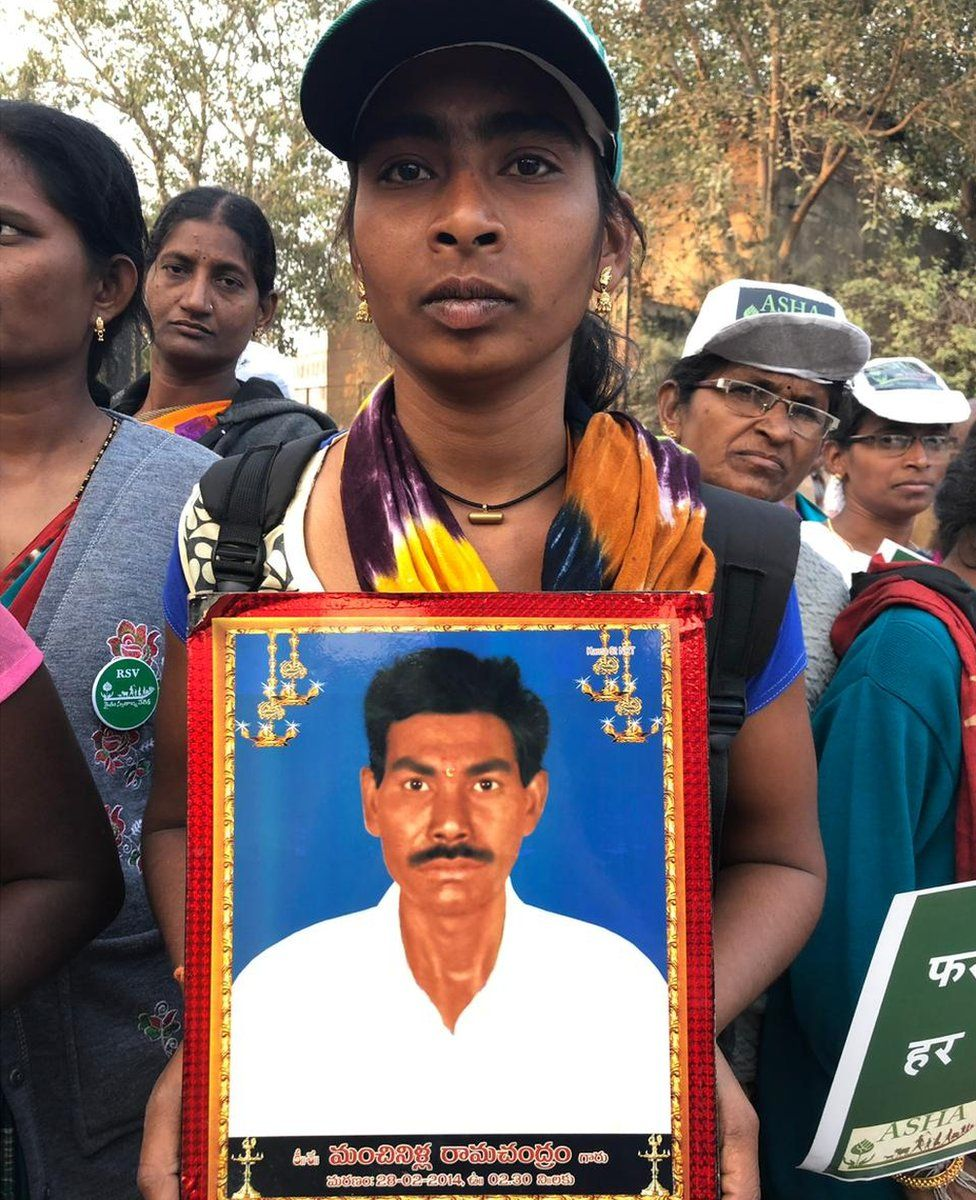 The daughter of a farmer who killed himself is seen in the protest, carrying a photograph of her father.