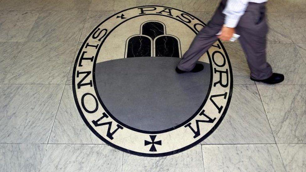 A man walks on a logo of the Monte Dei Paschi Di Siena bank
