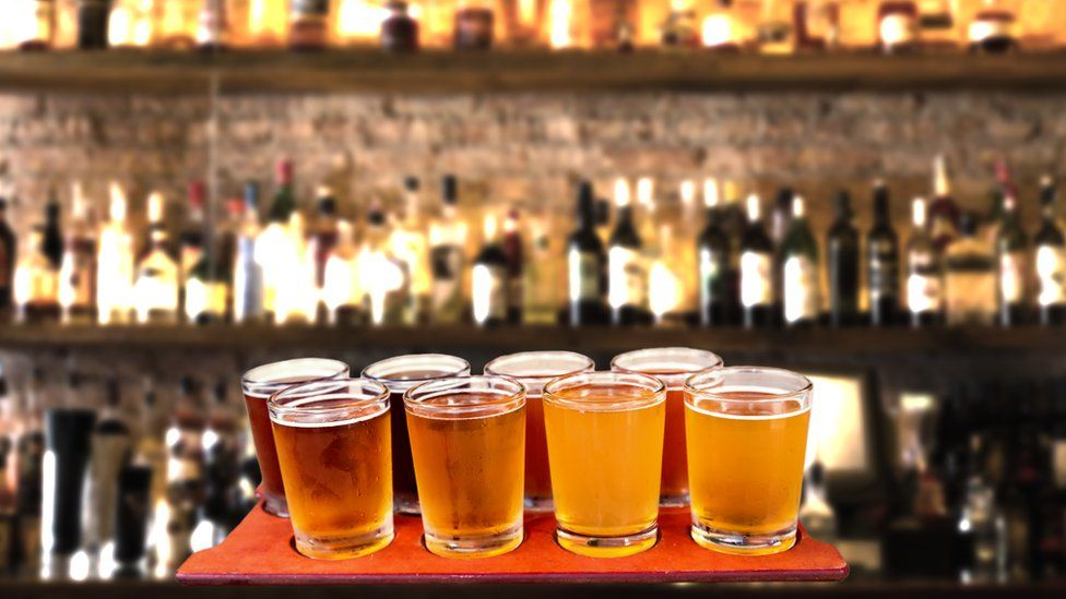 Beer flight of eight sampling glasses of craft beer on a bar countertop.